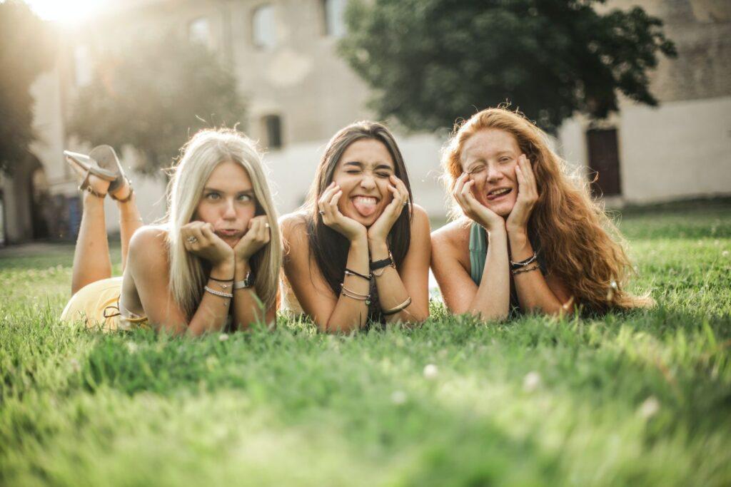 trzy uśmiechnięte dziewczyny leżą na trawie